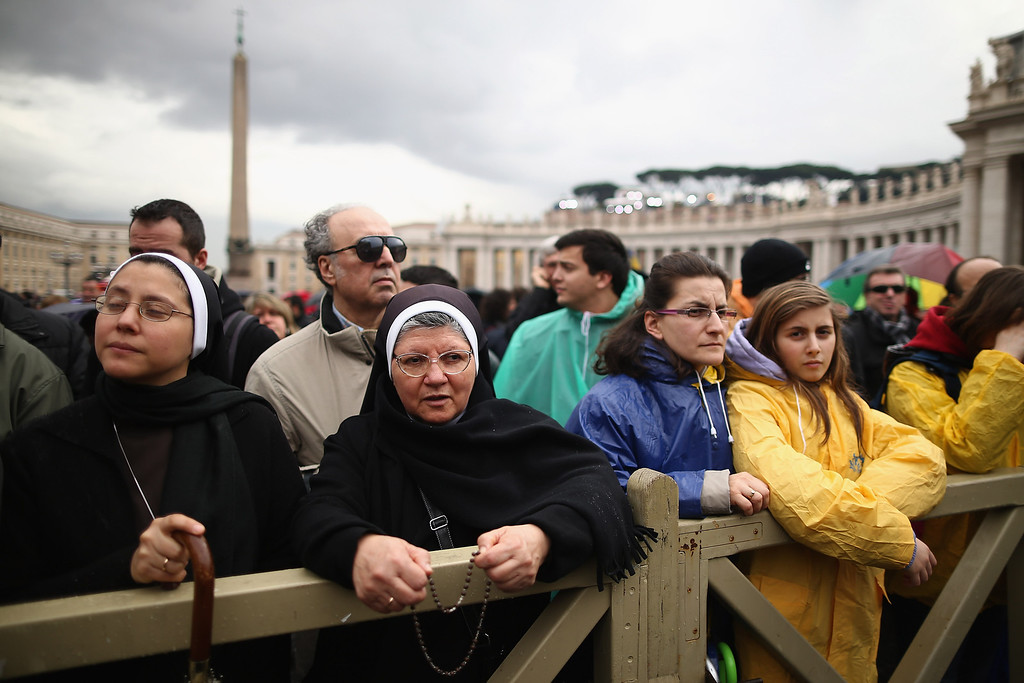 . People wait for smoke to emanate from the chimney on the roof of the Sistine Chapel which will indicate whether or not the College of Cardinals have elected a new Pope on March 13, 2013 in Vatican City, Vatican.  (Photo by Dan Kitwood/Getty Images)