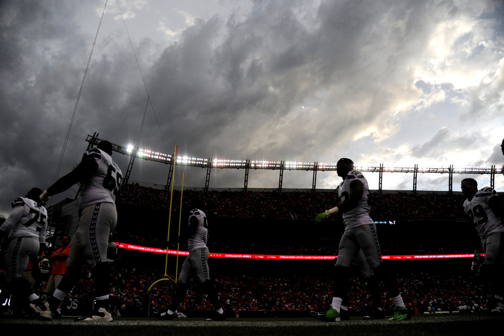 . Seattle Seahawks players walk off the field as a lightning delay takes effect during the first half of action at Sports Authority Field at Mile High. The Denver Broncos hosted the Seattle Seahawks in an NFL preseason game. (Photo by AAron Ontiveroz/The Denver Post)
