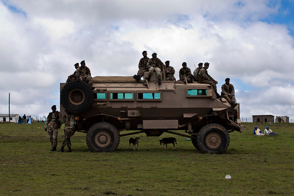 . South Africa army members sit atop of a military vehicle while some of them follow the burial ceremony of former South African President Nelson Mandela in his hometown Qunu, South Africa, Sunday Dec. 15, 2013. (AP Photo/Bernat Armangue)