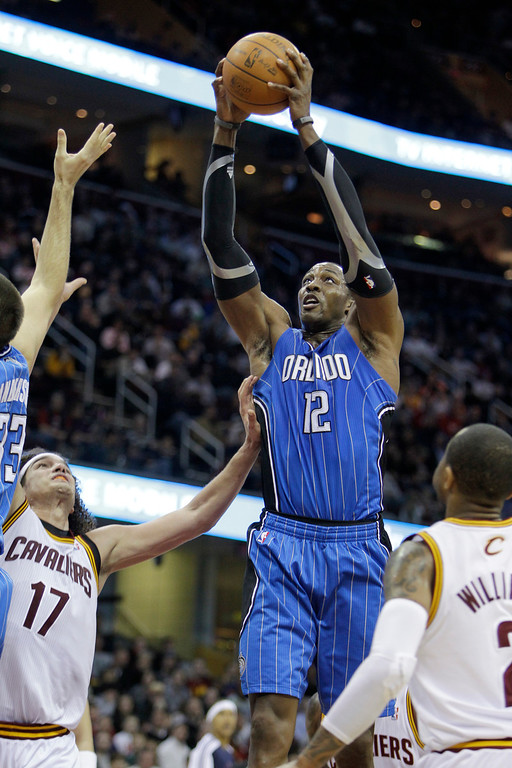 . Orlando Magic\'s Dwight Howard (12) grabs a rebound against Cleveland Cavaliers\' Anderson Varejao (17) and Mo Williams during an NBA basketball game Tuesday, Dec. 28, 2010, in Cleveland. (AP Photo/Mark Duncan)