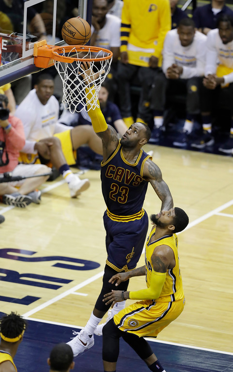 . Cleveland Cavaliers\' LeBron James scores over Indiana Pacers\' Paul George during the second half in Game 3 of a first-round NBA basketball playoff series, Thursday, April 20, 2017, in Indianapolis. Cleveland defeated Indiana 119-114. (AP Photo/Darron Cummings)