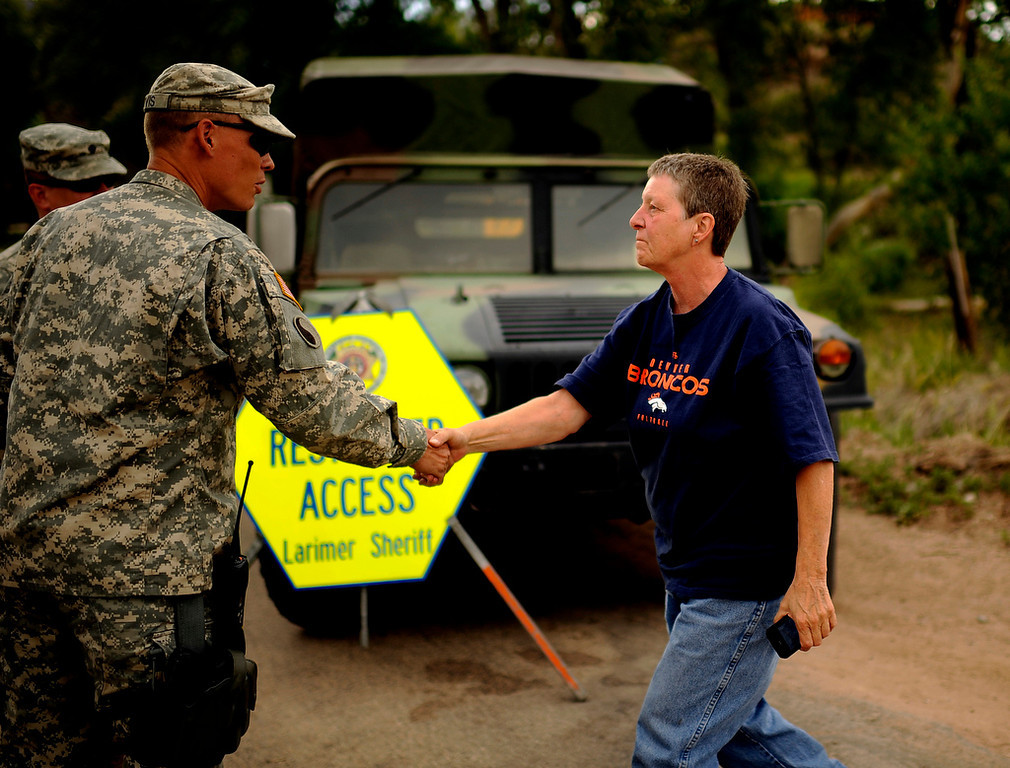 . Carole Prieskorn, an evacuee of Rist Canyon area, thanks to Army National Guard 193rd Military Police Specialist Randall Orvis at the Rist Canyon Road and County Road 27e road block for the High Park Fire west of Fort Collins on Friday, June 15, 2012. Hyoung Chang, The Denver Post