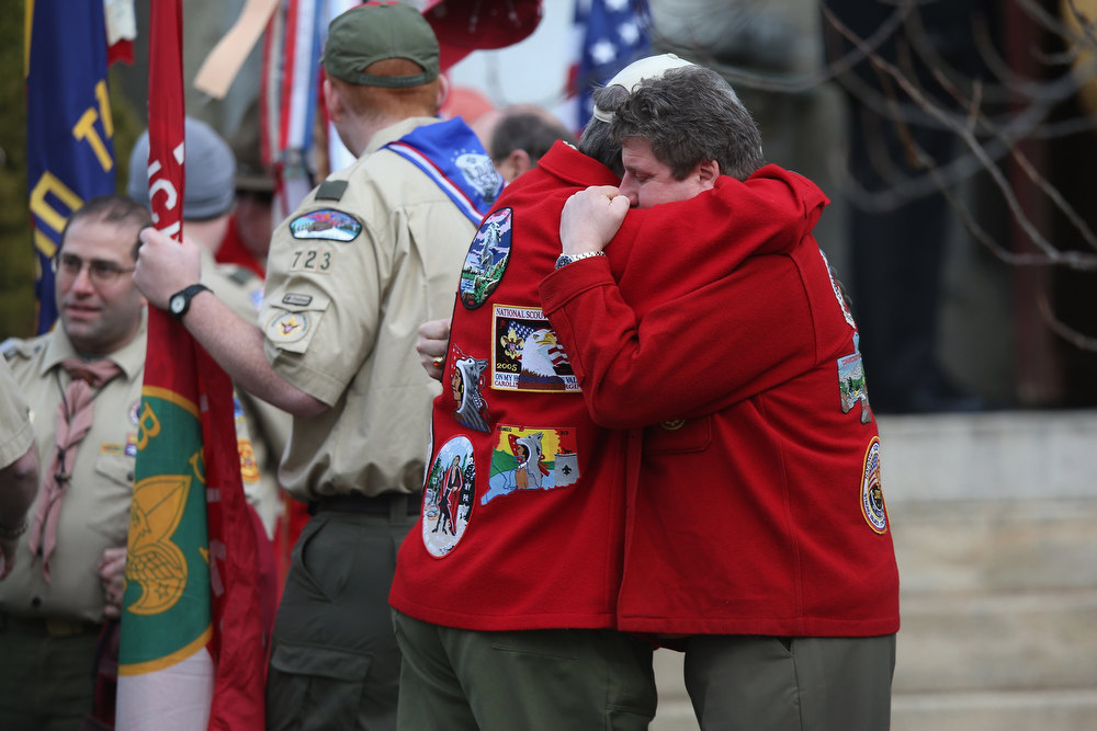 Description of . Mourners embrace following a funeral for Benjamin Wheeler, 6, at the Trinity Episcopal Church on December 20, 2012 in Newtown, Connecticut. Benjamin, a member of Tiger Scout Den 6, was killed when 20 children and six adults were massacred at Sandy Hook Elementary School last Friday. Six services were held for students and teachers in the Newtown area Thursday.  (Photo by John Moore/Getty Images)