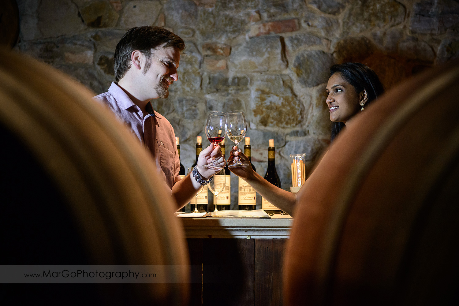 man in pink shirt and Indian woman in flower dress clink wine glasses in the wine cellar during engagement session at Castello di Amorosa in Calistoga