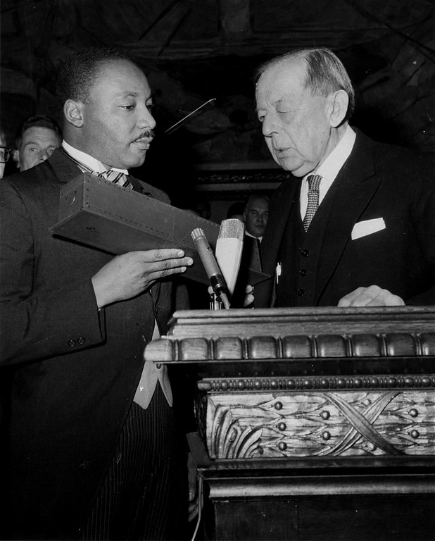 . Dr. Martin Luther King, Jr., American civil rights leader, holds a case containing the Nobel Peace Prize gold medal after the presentation in Oslo, Norway, December 10, 1964.  Gunnar Jahn, chairman of the Norwegian Parliament\'s Nobel Committee, makes the presentation.  King, 35, the youngest man ever to receive the prize, is the 12th American and the third black to be given the award.  (AP Photo)