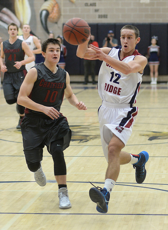 . LITTLETON, CO. - JANUARY 17: Dakota Ridge guard Jacob Flores (12) dished off the ball past Chargers defender Riley Welch (10) in the first half. The Dakota Ridge High School boy\'s basketball team hosted Chatfield Friday night, January 16, 2014. Photo By Karl Gehring/The Denver Post
