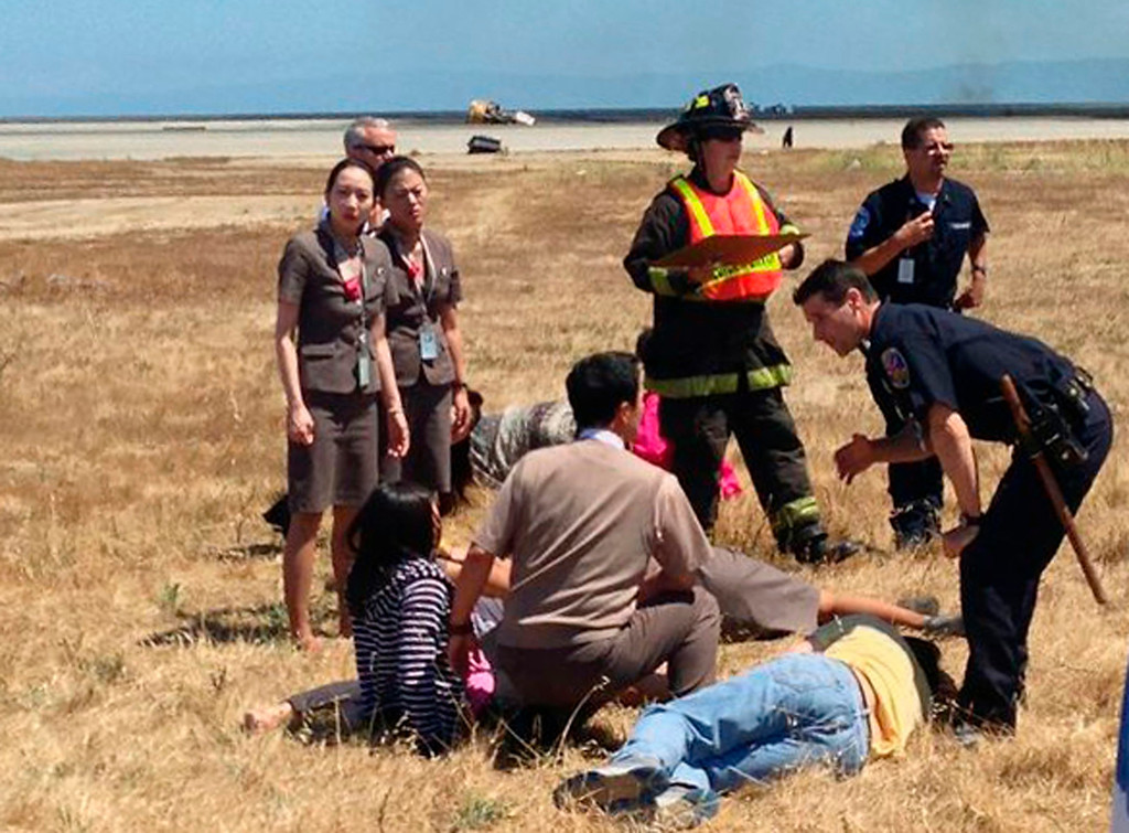 . Asiana Airlines flight attendant Kim Ji-yeon, left, stands near a runway with rescued passengers after flight 214 crash landed at San Francisco International Airport on July 6, 2013, in this photo provided by passenger Eugene Anthony Rah released to Reuters on July 8, 2013.  (Eugene Anthony Rah via Reuters)