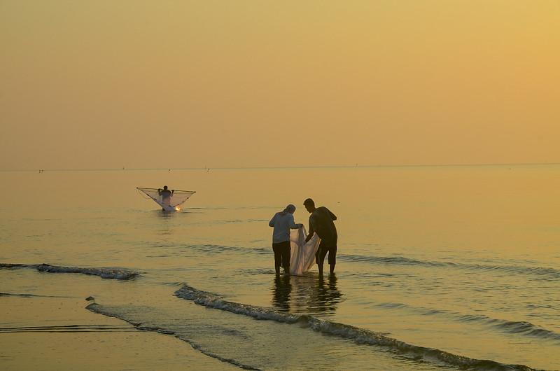 Tropical sunrise seascape with men hand net fishing, Thailand.