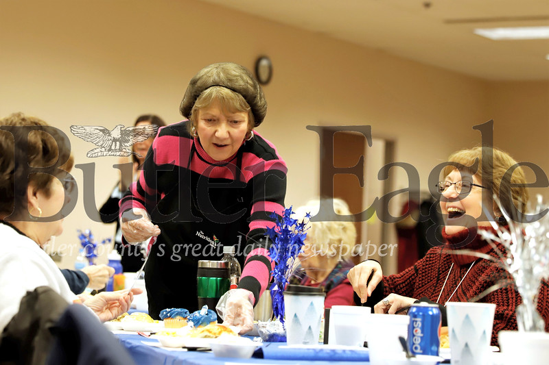Nettie Culley serves up cupcakes to Peggy Kratz (right) and other members at the Cranberry Senior Center Winter Blues Party Thursday. Seb Foltz/Butler Eagle 01/23/20