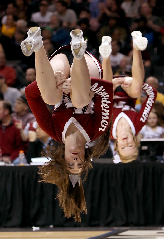 . Massachusetts Minutemen cheerleaders do backflips in the first half against the George Washington Colonials during the Quarterfinals of the 2014 Atlantic 10 Men\'s Basketball Tournament at Barclays Center on March 14, 2014 in the Brooklyn Borough of New York City.  (Photo by Mike Lawrie/Getty Images)