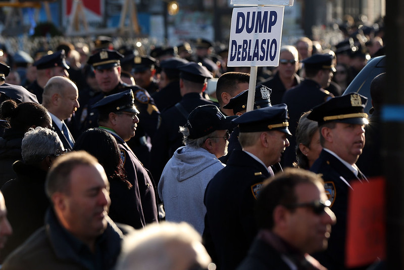 . An anti Mayor Bill de Blasio protester holds up a sign outside of  Christ Tabernacle Church for the funeral of slain New York City Police Officer Rafael Ramos, one of two officers murdered while sitting in their patrol car in an ambush in Brooklyn last Saturday afternoon on December 27, 2014 in New York City. Thousands of fellow officers, family, friends and Vice President Joseph Biden are expected at the church in the Glendale neighborhood of Queens for the funeral.  (Photo by Spencer Platt/Getty Images)