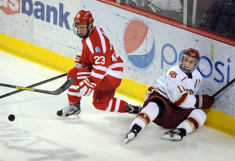 . University of Denver\'s Chris Knowlton, right, is checked by Boston University\'s Matt Lane in the 2nd period of the game at Magness Arena in Denver, Colo. on Saturday, December 29, 2012. Hyoung Chang, The Denver Post