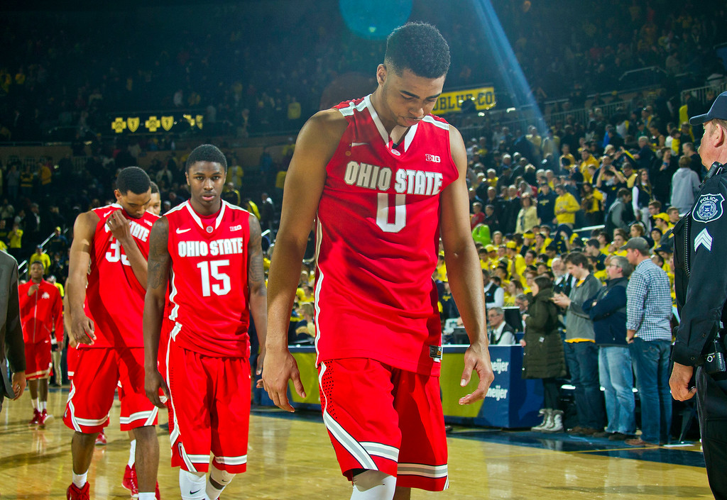 . Ohio State guard D\'Angelo Russell (0), guard Kam Williams (15) and teammates walk off the court after losing an NCAA college basketball game 64-57 to Michigan, Sunday, Feb. 22, 2015, in Ann Arbor, Mich. (AP Photo/Tony Ding)