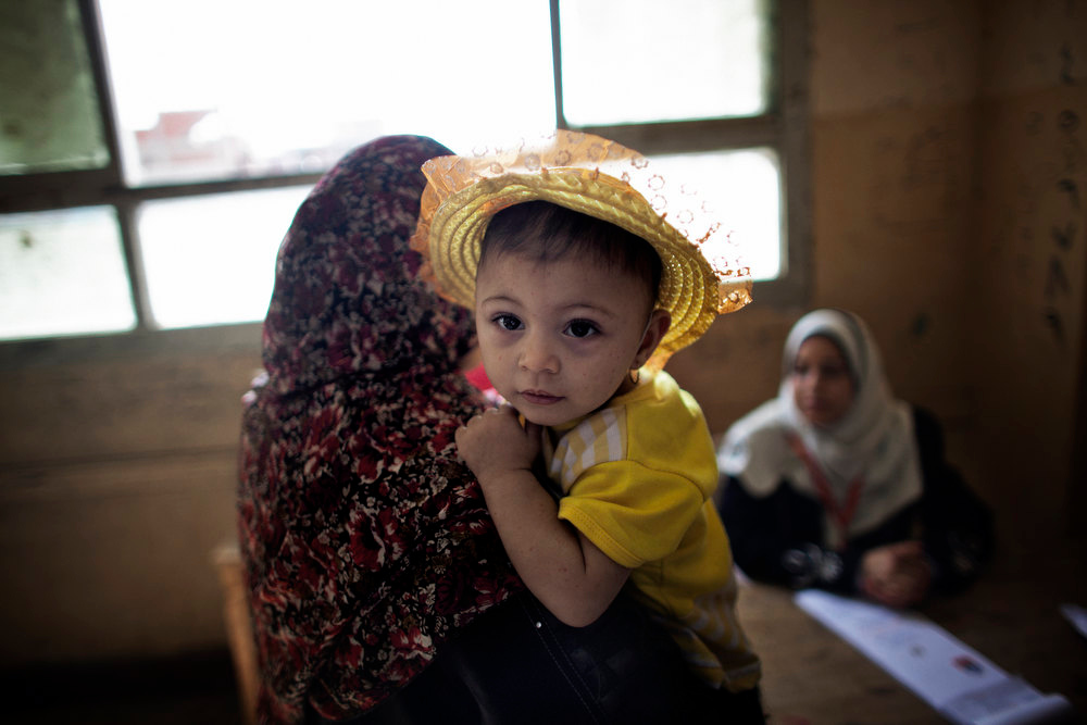 Description of . An Egyptian woman holds her daughter while picking up her ballot at a polling station in the rural village of Namul, 60km north of Cairo, on May 24, 2012, on the second day of the Presidential elections. MARCO LONGARI/AFP/Getty Images