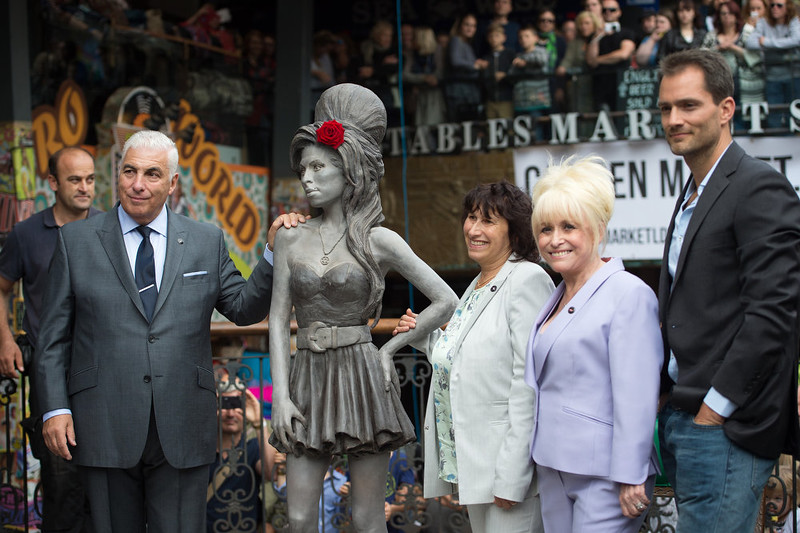 . Mitch Winehouse, left, and Janis Winehouse, pose for a picture with a statue of their late daughter, Amy Winehouse, with actor Barbara Windsor, second right, and the artist Scott Eaton, right, after it was unveiled in Camden\'s Stables Market, in London, England, Sunday, Sept. 14, 2014. Three years after her death the unveiling coincides with what would have been her 31st birthday. (AP Photo/Tim Ireland)