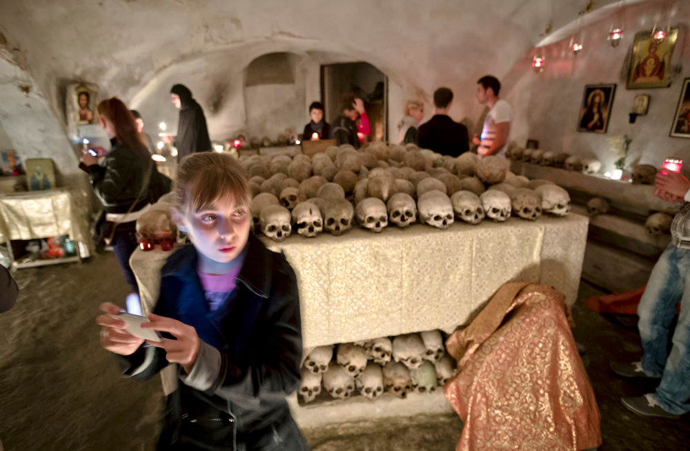 . A child takes pictures in the ossuary at the Pasarea monastery, outside Bucharest, Romania, Sunday, May 5, 2013 after the Easter Religious service. The ossuary, containing mostly remains of the nuns that lived at the monastery is briefly opened on Easter night. (AP Photo/Vadim Ghirda)