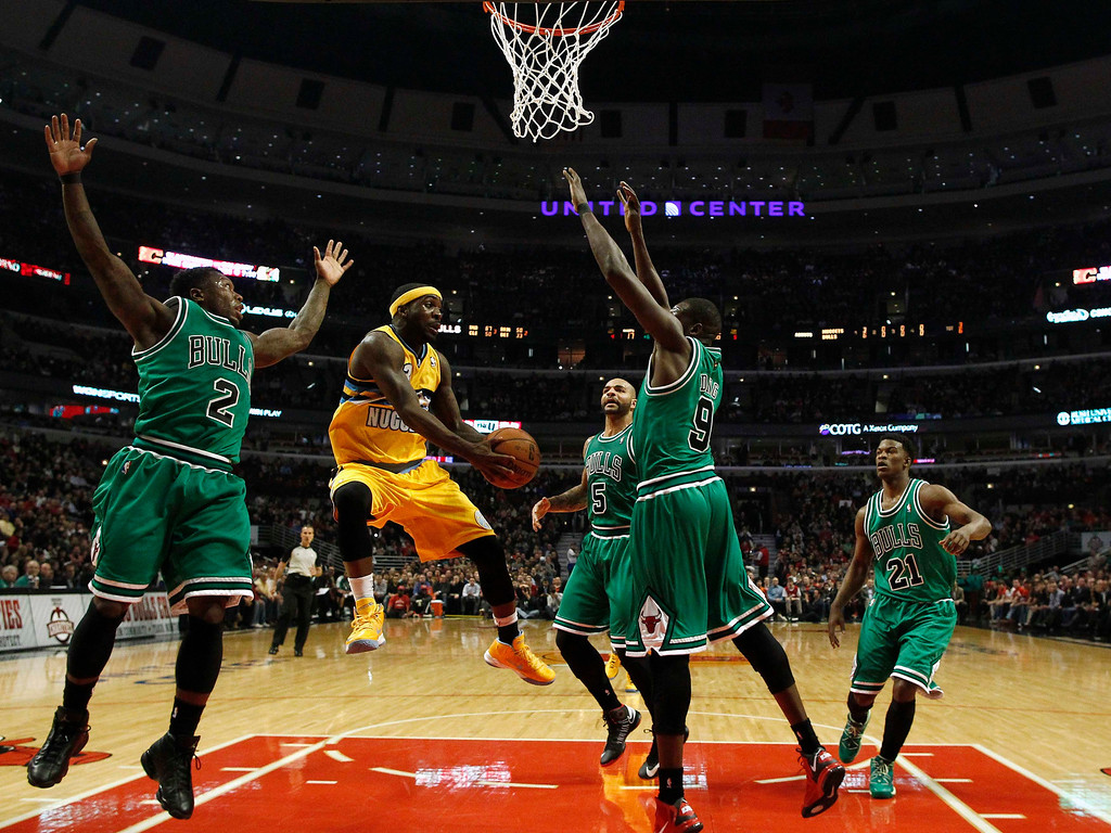 . Denver Nuggets\' Ty Lawson (2nd L) goes to the basket against the Chicago Bulls\' Nate Robinson (L), Carlos Boozer (C), Luol Deng (2nd R) and Jimmy Butler during the first half of their NBA basketball game in Chicago, Illinois, March 18, 2013.  REUTERS/Jim Young