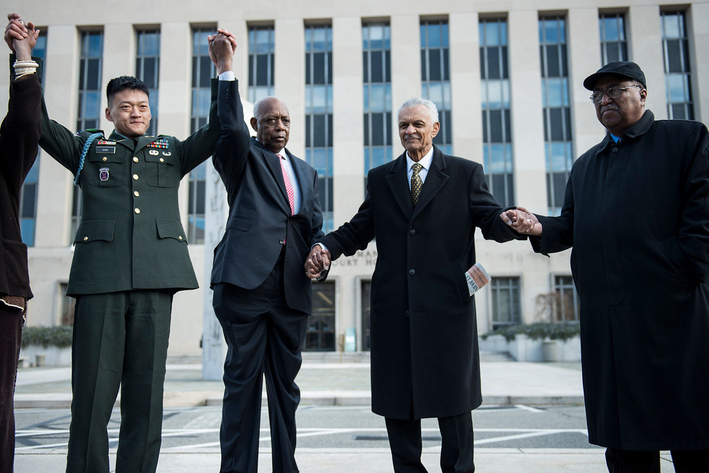 """. Former US Army Lt. Dan Choi(L), a gay rights activist and opponent of \""""Don\'t ask Don\'t Tell\"""", stands with Joe Beasley (2L), of the Rainbow Push, American Civil Rights era icon Reverend C.T. Vivian (2R) and Dr. Charles Steele Jr. (R), Chief Executive Officer of the Southern Christian Leadership Conference at the E. Barrett Prettyman Federal Courthouse March 28, 2013 in Washington, DC. The trial of Choi, which began in August 2011, resumes Thursday in federal court. The former Iraq War vet and graduate of West Point is going to trial to face charges that stem from a November 2010 arrest for chaining himself to the White House fence to protest Don\'t Ask, Don\'t Tell. BRENDAN SMIALOWSKI/AFP/Getty Images"""