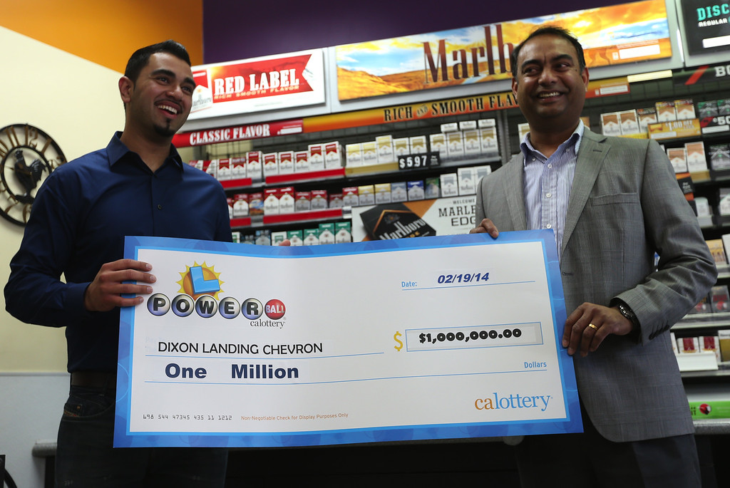 . Parmeet Singh, the Dixon Landing Chevron gas station owners\'s son, and his uncle Karam Singh,  vice president of operations, from left, are presented with an oversized check for $1 million in Milpitas, Calif., on Thursday, Feb. 20, 2014. The owners received the prize for having sold a winning Powerball lottery ticket worth $425 million. (Anda Chu/Bay Area News Group)