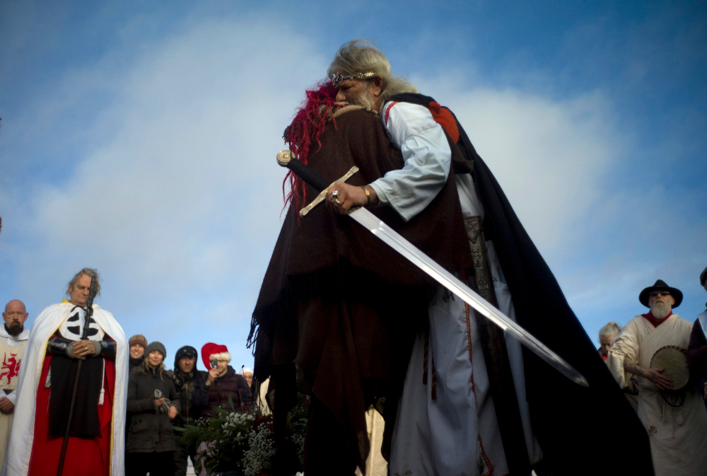 Description of . Druid Arthur Pendragon hugs a reveller during the winter solstice at Stonehenge on Salisbury plain in southern England December 21, 2012. The winter solstice is the shortest day of the year, and the longest night of the year. REUTERS/Kieran Doherty
