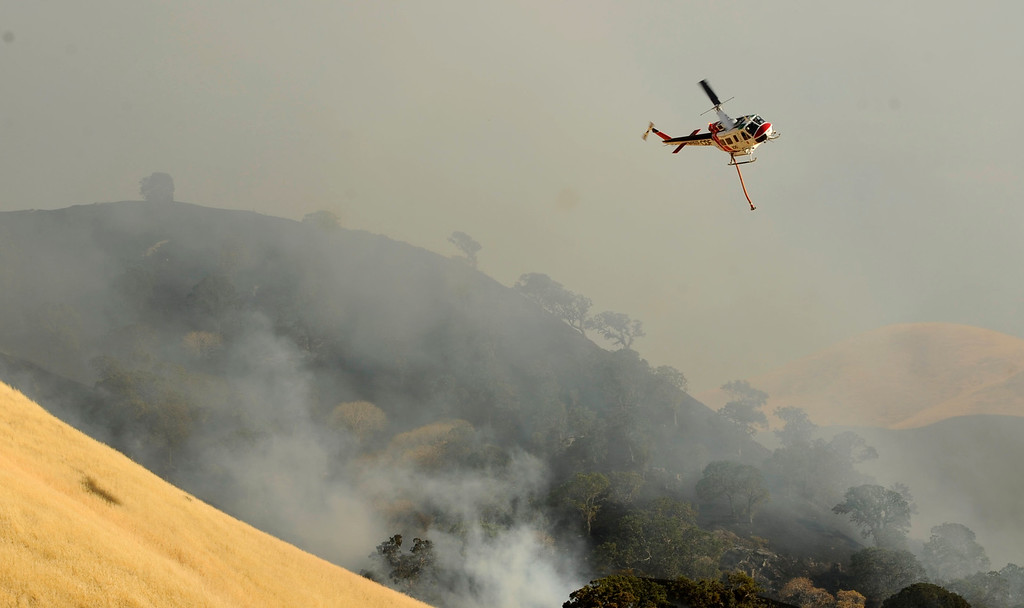 . A vegetation fire moves up a canyon near Foothill Dr. where a helicopter has just released water onto the blaze  in Antioch, Calif., on Wednesday, June 24, 2015. (Susan Tripp Pollard/Bay Area News Group)