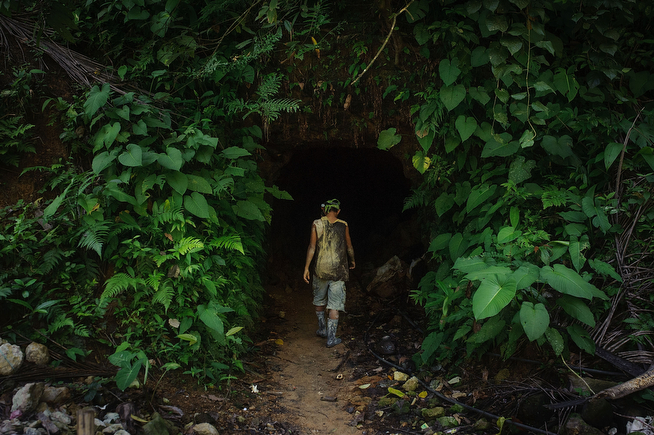 . A 14-year-old miner enters a dark tunnel after taking a short break. (Photo by Luc Forsyth/Getty Images)
