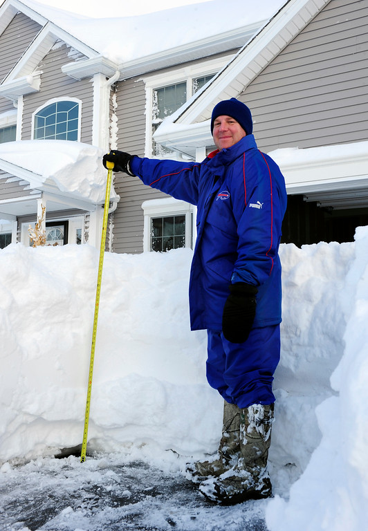 . Art Hauret pauses after he measures the nearly four foot accumulation of snow in his driveway on Summerfield Drive in Lancaster, N.Y. Wednesday, Nov. 19, 2014.  A ferocious storm dumped massive piles of snow on parts of upstate New York, trapping residents in their homes and stranding motorists on roadways, as temperatures in all 50 states fell to freezing or below.   (AP photo/Gary Wiepert)