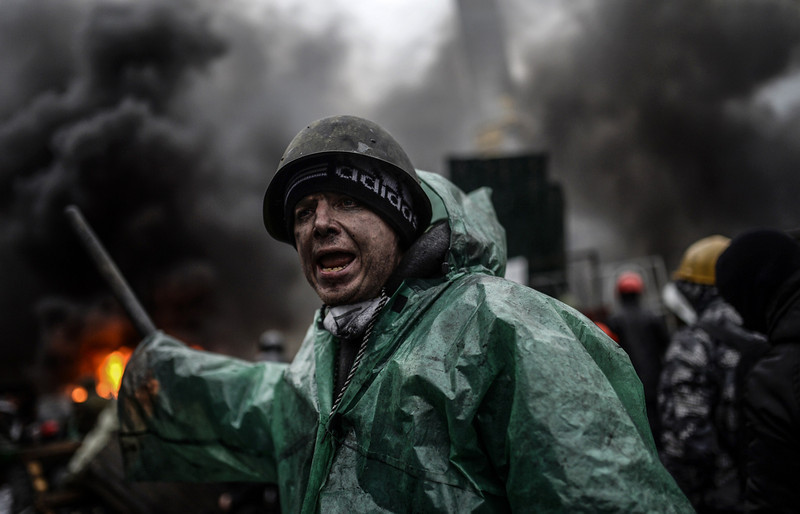 """. A protester stands behind barricades during clashes with police on February 20, 2014 in Kiev. Ukraine\'s embattled leader announced a \""""truce\"""" with the opposition as he prepared to get grilled by visiting EU diplomats over clashes that killed 26 and left the government facing diplomatic isolation. The shocking scale of the violence three months into the crisis brought expressions of grave concern from the West and condemnation of an \""""attempted coup\"""" by the Kremlin. At least 25 protesters were killed on February 20 in fresh clashes between thousands of demonstrators and heavily-armed riot police in the heart of Kiev, AFP correspondents at the scene said. The bodies of eight demonstrators were lying outside Kiev\'s main post office on Independence Square, an AFP reporter said. The bodies of 17 other demonstrators with apparent gunshot wounds were also seen in the vicinity of two hotels on opposite sides of the protest encampment. BULENT KILIC/AFP/Getty Images"""
