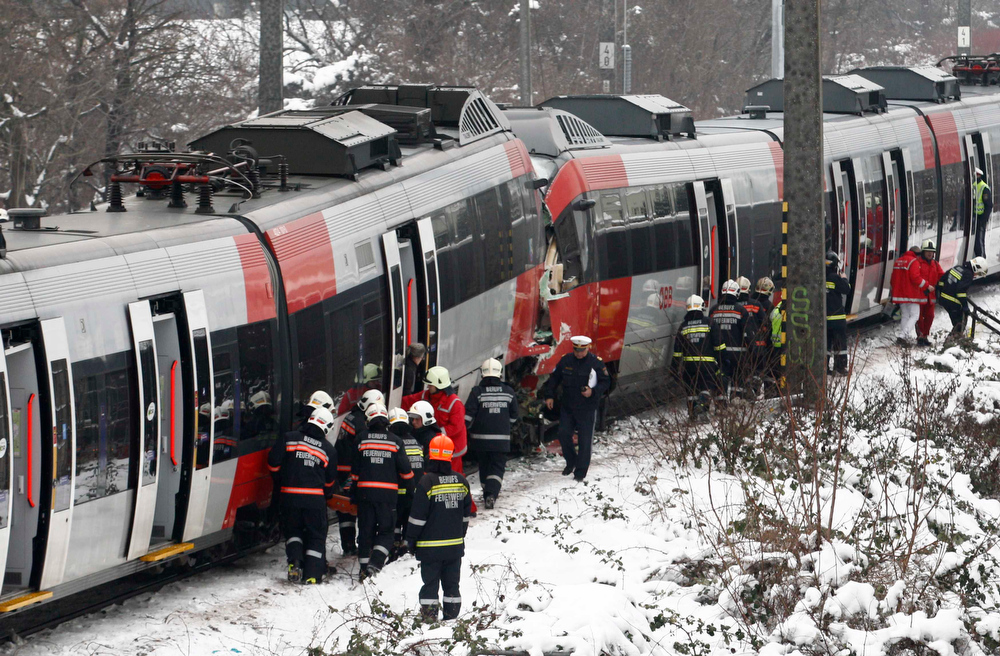 . Austrian rescue personnel stands in front of two demolished S45 trains after a train crash in Vienna January 21, 2013. Two  trains collided Monday morning, injuring 25 people, police said. REUTERS/Heinz-Peter Bader  (AUSTRIA - Tags: DISASTER TRANSPORT)