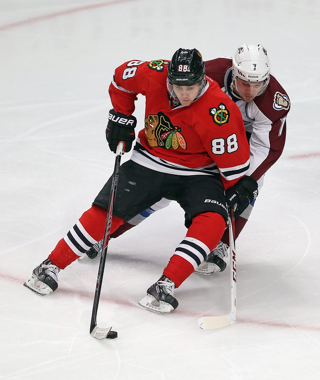 . CHICAGO, IL - DECEMBER 27: John Mithcell #7 of the Colorado Avalanche shadows Patrick Kane #88 of the Chicago Blackhawks at the United Center on December 27, 2013 in Chicago, Illinois. The Blackhawks defeated the Avalanche 7-2. (Photo by Jonathan Daniel/Getty Images)