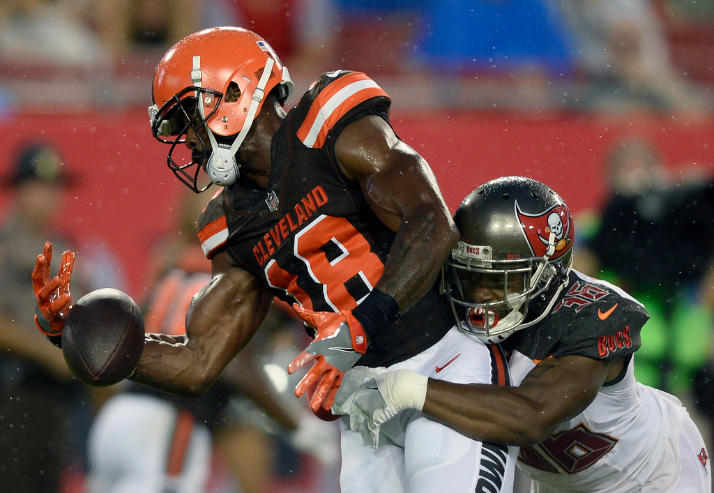 . Cleveland Browns wide receiver Kenny Britt (18) loses the football when he is hit by Tampa Bay Buccaneers defensive back Robert McClain (36) during the first quarter of an NFL preseason football game Saturday, Aug. 26, 2017, in Tampa, Fla. (AP Photo/Jason Behnken)