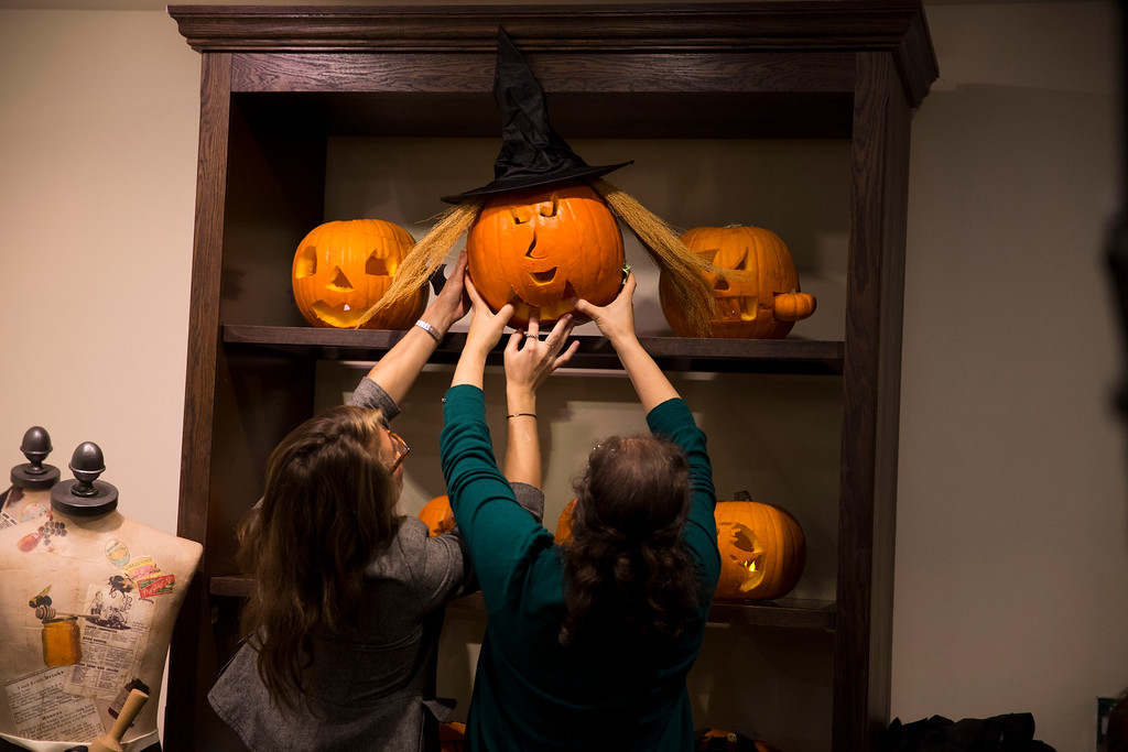. An entry is lifted into place to be displayed for judging in a children\'s pumpkin carving competition at the Fortnum & Mason department store in London, Thursday, Oct. 31, 2013. Pumpkins are traditionally carved with decorative faces by people to mark Halloween which occurs annually around the world on October 31. (AP Photo/Matt Dunham)