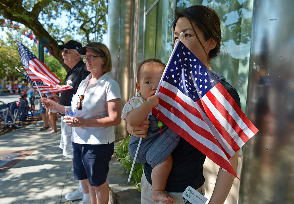 . Kokoro Motegi, of Orinda, holds her daughter Sophie, 9 months old, as they stand during the playing of the national anthem before the start of the 30th anniversary Lamorinda Fourth of July parade and celebration on Thursday, July 4, 2013. (Jose Carlos Fajardo/Bay Area News Group)