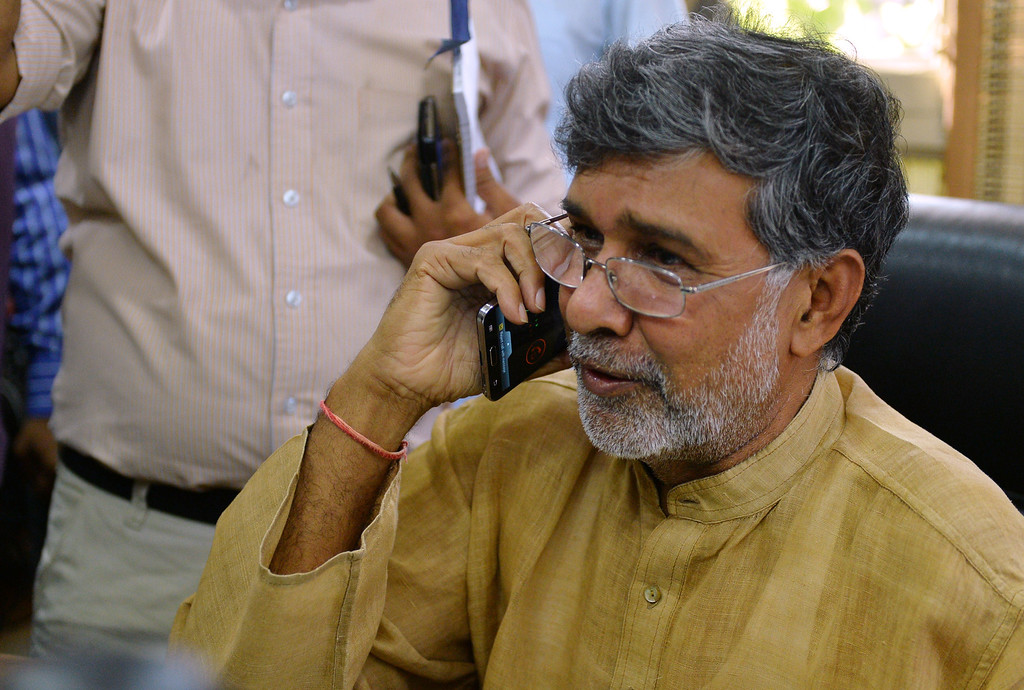 . Indian activist Kailash Satyarthi talks over his mobile phone at this home office after the announcement of him receiving the Nobel Peace Prize, in New Delhi on October 10, 2014. Indian activist Kailash Satyarthi said October 10 his Nobel Peace Prize would help highlight the plight of children around the world, and invited fellow winner Malala Yousafzai to work with him. AFP PHOTO / CHANDAN  Khanna/AFP/Getty Images