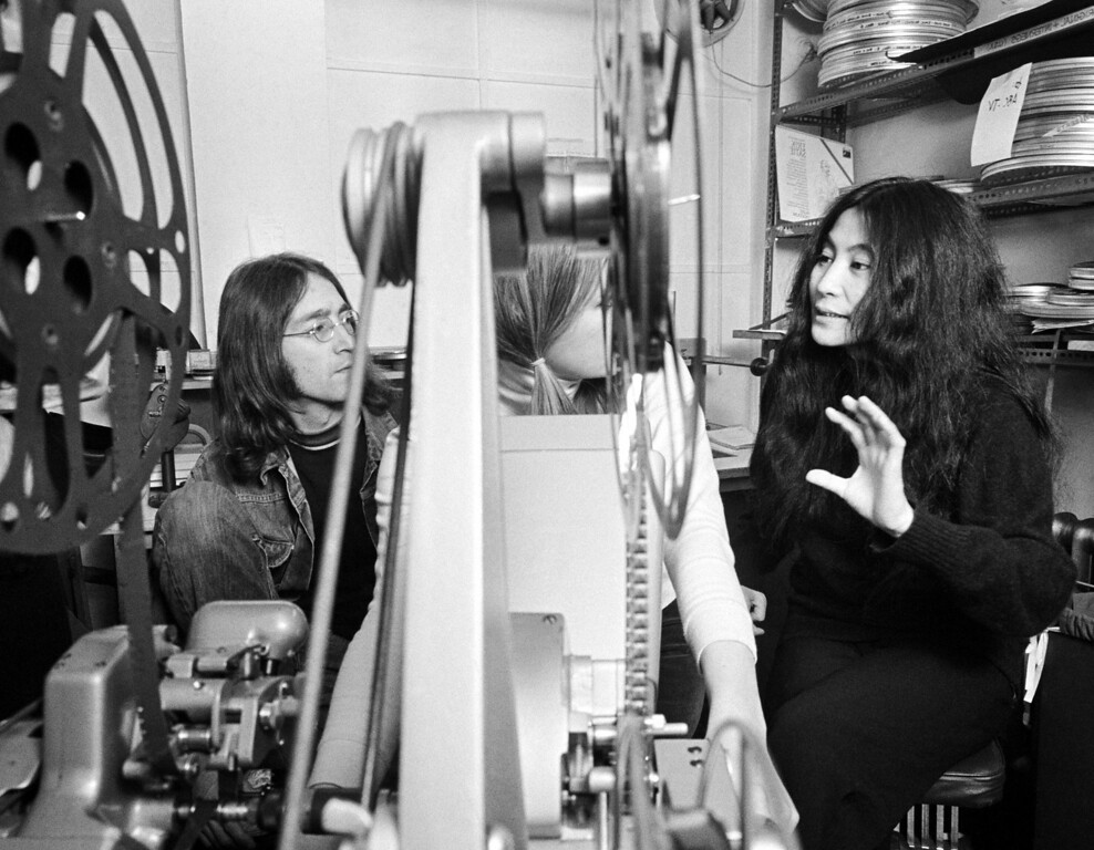 """. Beatle John Lennon, left, and his friend Japanese actress Yoko Ono go through the editing of the film \""""Rape\"""" together with an editor, partly obscured by the viewer Reel, in London, England, on Feb. 5, 1969. (AP Photo)"""