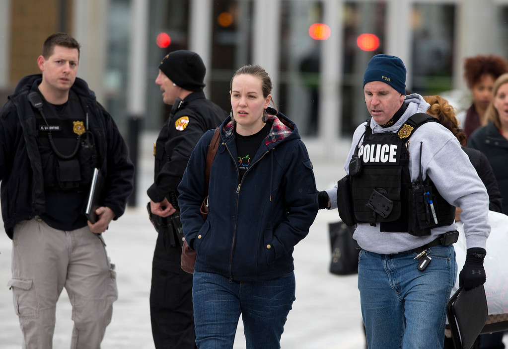 . Police and law enforcement evacuate The Mall of Columbia after a shooting Saturday, Jan. 25, 2014, in Columbia, Md. Police say three people died in a shooting at the mall in suburban Baltimore, including the presumed gunman. (AP Photo/ Evan Vucci)