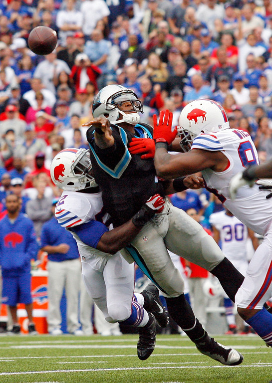 . Carolina Panthers quarterback Cam Newton throws as he is hit by Buffalo Bills outside linebacker Arthur Moats, left, and defensive end Mario Williams in the second half on an NFL football game Sunday, Sept. 15, 2013, in Orchard Park, N.Y. (AP Photo/Bill Wippert)