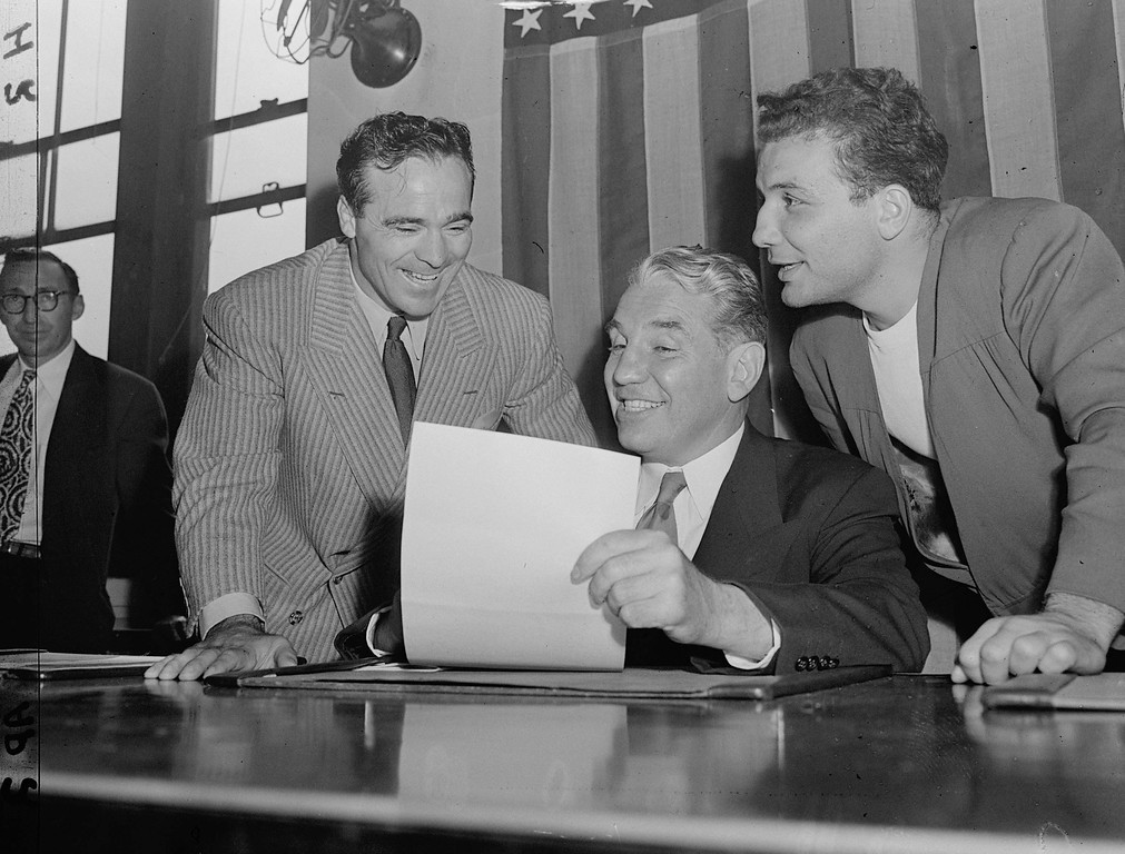 . Eddie Eagan, center, chairman of the New York State Athletic Commission, studies a contract with middleweight boxing champion, Jake LaMotta, right, of the Bronx, and former middleweight king, Marcel Cerdan in New York City on September 15, 1949.  (AP Photo)