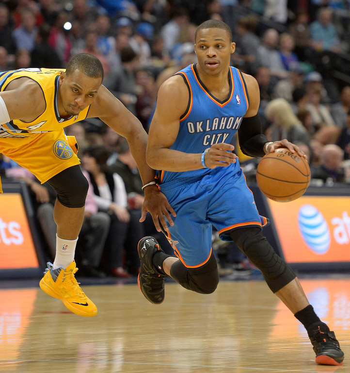 . Oklahoma City Thunder point guard Russell Westbrook (0) drives past Denver Nuggets shooting guard Randy Foye (4) during the third quarter December 17, 2013 at Pepsi Center. (Photo by John Leyba/The Denver Post)