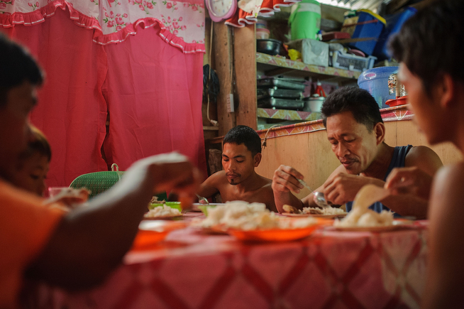 . Gold miners and their family eat dinner together in a small house built near their mountainside camp. Many miners have homes in the nearby village of Pinut-An, but stay in the mountain camp to be closer to their tunnel, on April 22, 2014 in Pinut-An, Philippines. (Photo by Luc Forsyth/Getty Images)
