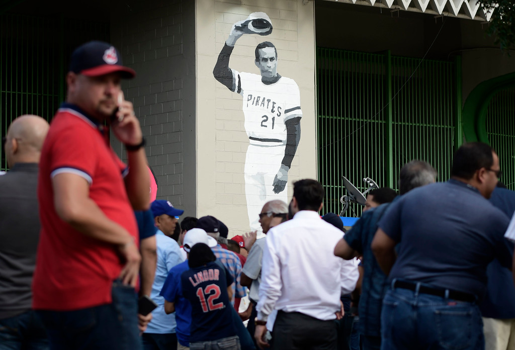 . A mural of Puerto Rican professional baseball right fielder Roberto Clemente decorates Hiram Bithorn Stadium where fans wait to enter the final game of a two-game Mayor League Series between the Minnesota Twins and the Cleveland Indians in San Juan, Puerto Rico, Wednesday, April 18, 2018. (AP Photo/Carlos Giusti)