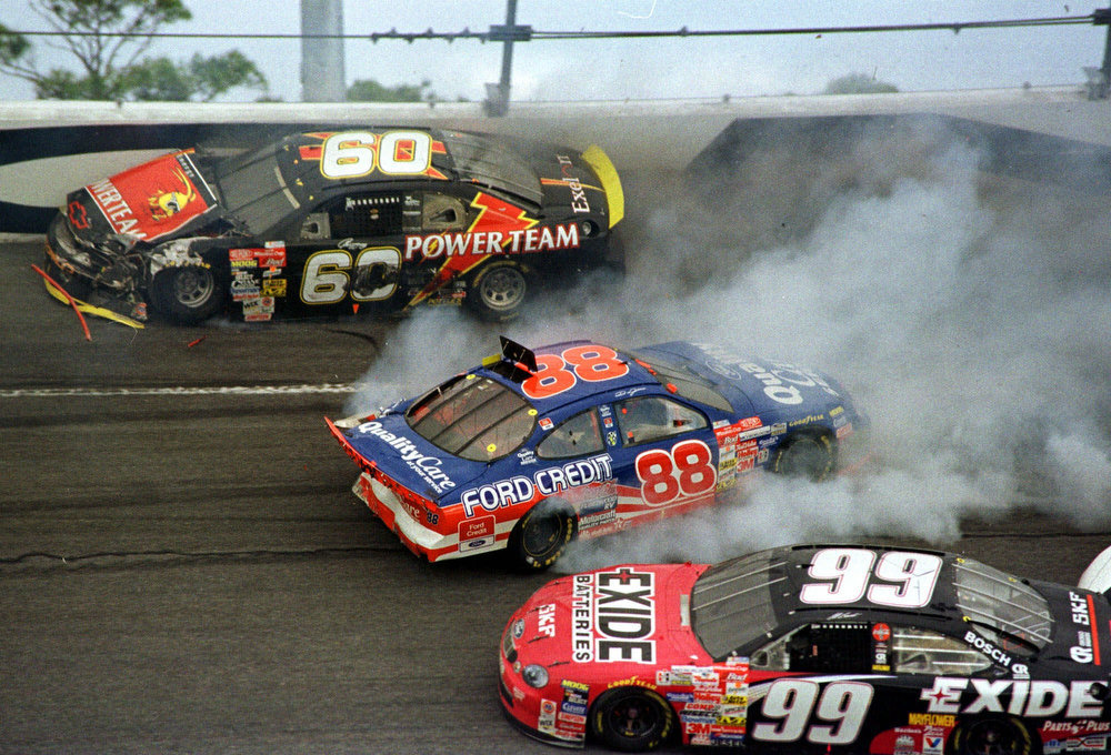 Description of . Geoff Bodine of Chemung, NY., (60) hits the wall in turn four while Dale Jarrett of Hickory, N.C., (88) spins as Jeff Burton of South Boston, Va., (99) manages to get by during the Daytona 500 Sunday, Feb. 14, 1999 at the Daytona International Speedway in Daytona Beach, Fla. (AP Photo/Rob Sweeten)