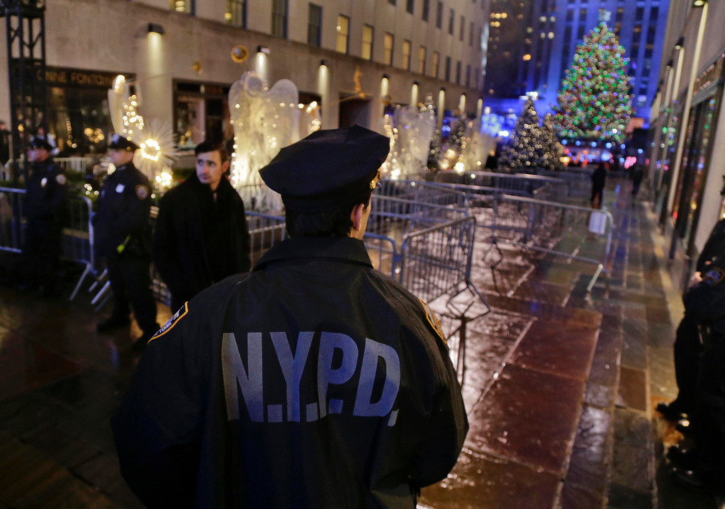 . New York Police officers stand watch at an entrance to Rockefeller Center along Fifth Avenue where the Rockefeller Center Christmas tree could be seen after the lighting ceremony, Wednesday, Dec. 2, 2015, in New York. Increased security surrounded the annual event, which drew several thousand spectators. (AP Photo/Julie Jacobson)