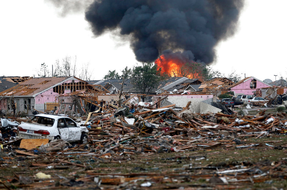 . A fire burns in the Tower Plaza Addition in Moore, Okla., following a tornado Monday, May 20, 2013. A tornado as much as a mile (1.6 kilometers) wide with winds up to 200 mph (320 kph) roared through the Oklahoma City suburbs Monday, flattening entire neighborhoods, setting buildings on fire and landing a direct blow on an elementary school. (AP Photo Sue Ogrocki)