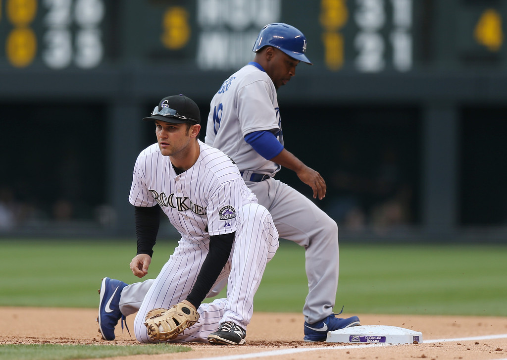 . Colorado Rockies first baseman Ryan Wheeler, front, fields pickoff throw as Los Angeles Dodgers\' Chone Figgins returns to first base in the first inning of a baseball game in Denver on Sunday, June 8, 2014. (AP Photo/David Zalubowski)