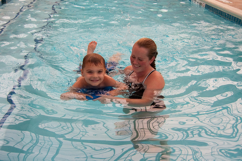 KC at swim lessons with his instructor learning how to kick on the kick board.