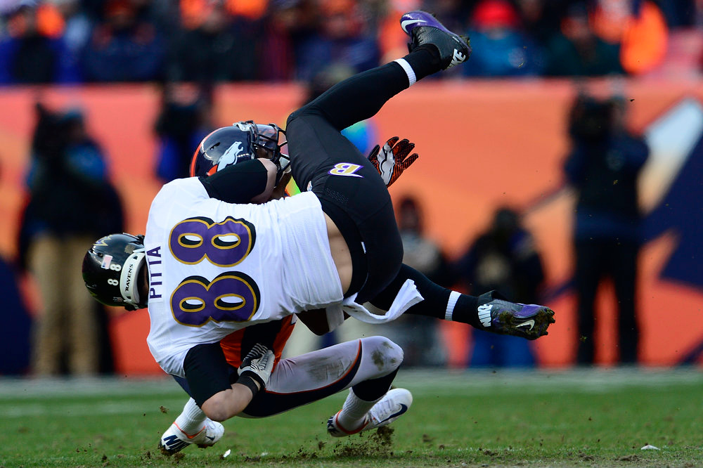 . Baltimore Ravens tight end Dennis Pitta (88) is taken down by Denver Broncos free safety Rahim Moore (26) after catching a 16-yard pass in the first quarter. The Denver Broncos vs Baltimore Ravens AFC Divisional playoff game at Sports Authority Field Saturday January 12, 2013. (Photo by AAron  Ontiveroz,/The Denver Post)