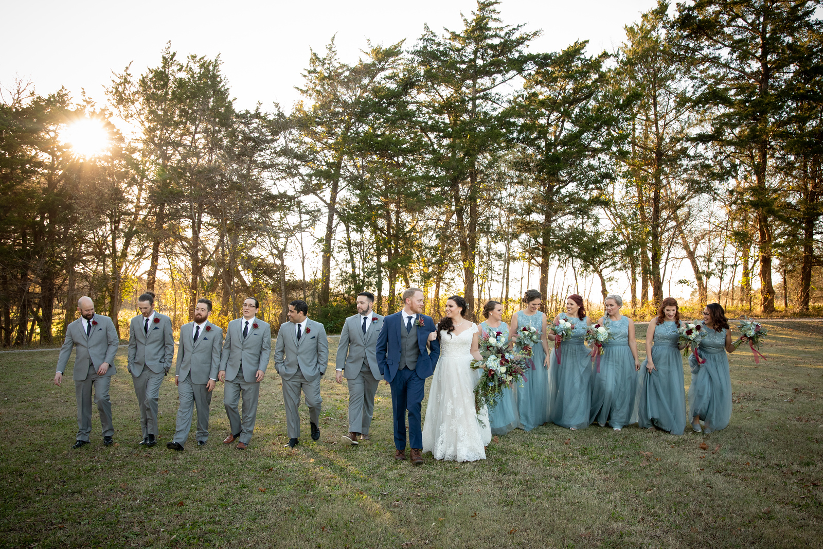 six groomsmen wearing grey suits groom wearing navy suit bride wearing white a-line gown six bridesmaids wearing tiffany blue dresses all walking in a line