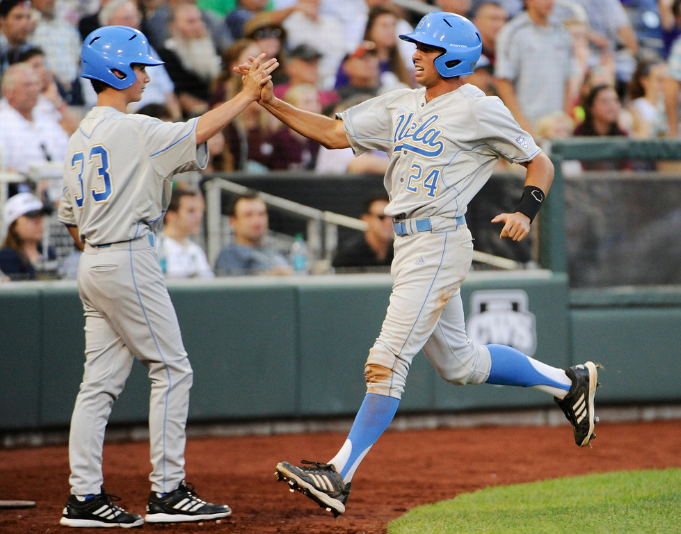 . UCLA\'s Brian Carroll (24) celebrates with teammate Hunter Virant after he scored against Mississippi State on a two-RBI single by Eric Filia in the fourth inning of Game 1 in their NCAA College World Series baseball finals, Monday, June 24, 2013, in Omaha, Neb. Brenton Allen also scored on the play. (AP Photo/Francis Gardler)
