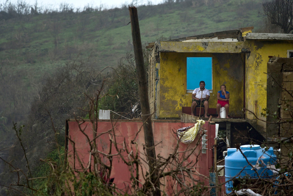 . A couple is seen from the distance sitting in their home in El Negro community a day after the impact of Hurricane Maria, in Puerto Rico, Thursday, September 21, 2017. As of Thursday evening, Maria was moving off the northern coast of the Dominican Republic with winds of 120 mph (195 kph). The storm was expected to approach the Turks and Caicos Islands and the Bahamas late Thursday and early Friday. (AP Photo/Carlos Giusti)